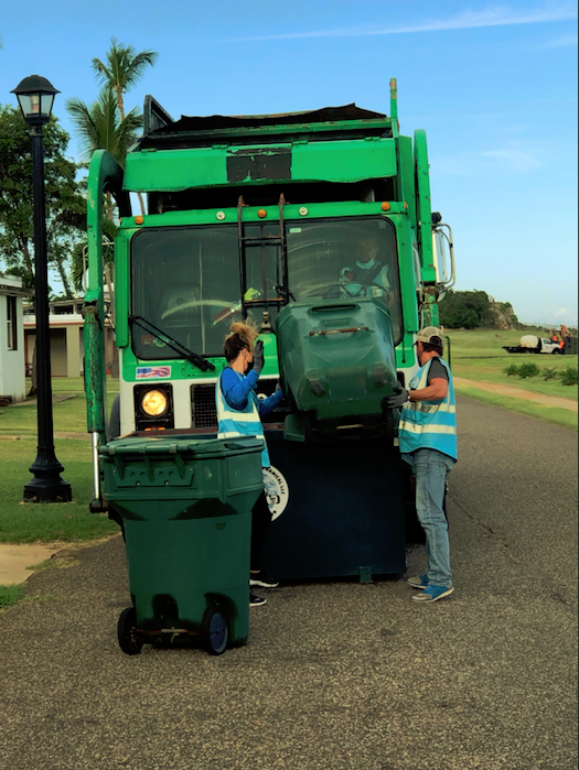Two workers unloading residential waste into a truck